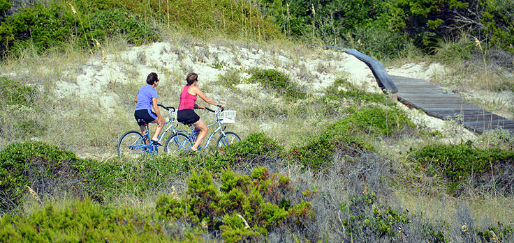 A couple rides bikes along the road on Bald Head Island NC