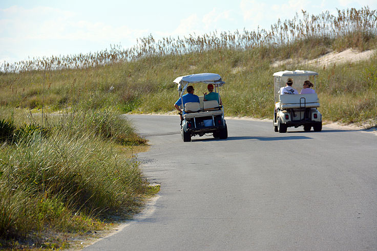 Golf carts pass each other on Bald Head Island, NC