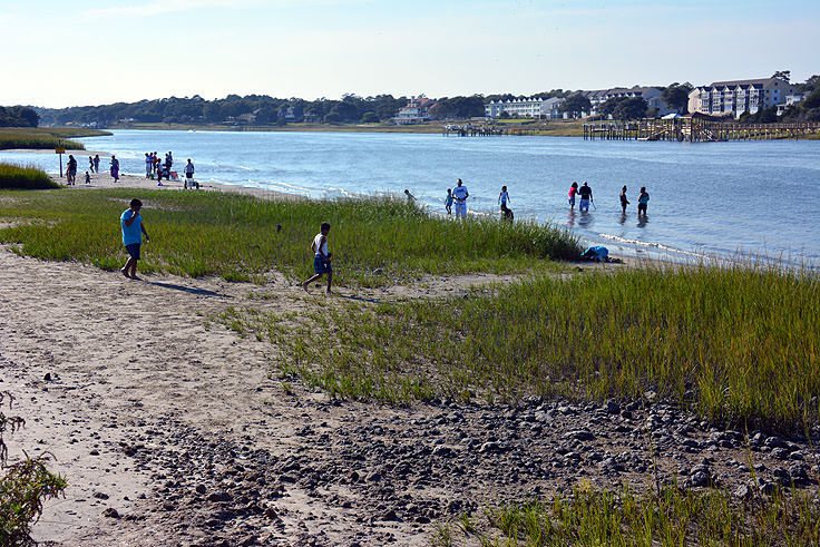 Families fish and play in the water at Ocean Isle Beach
