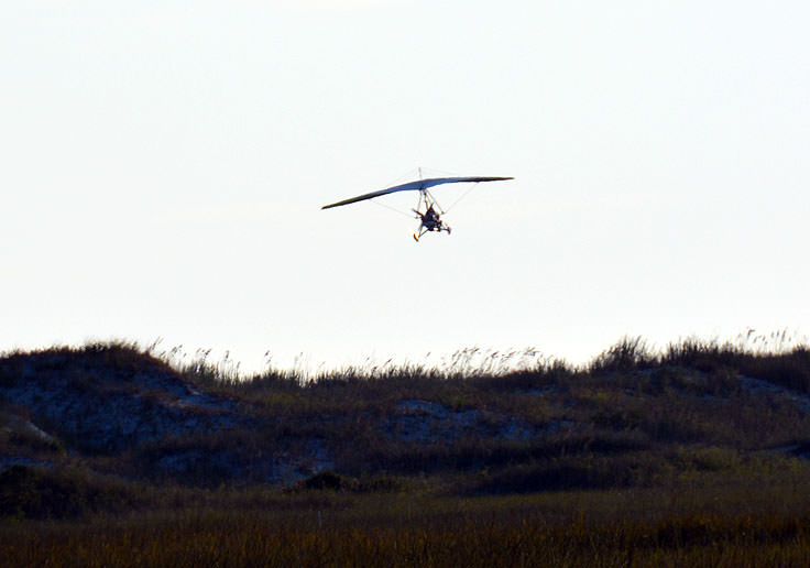 An ultralight aircraft flies over Sunset Beach, NC